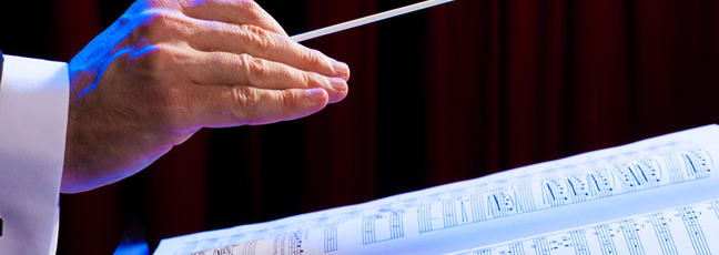 A photograph of a conductor's hand over the notation of a musical score