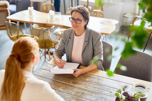Two women sit at the table in an informal interview situation.