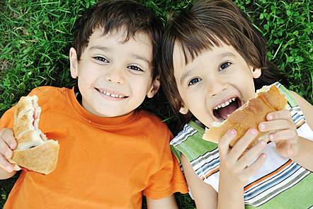 Two boys laying on ground in nature and happily eating healthy food