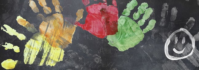 School blackboard with colourful handprints