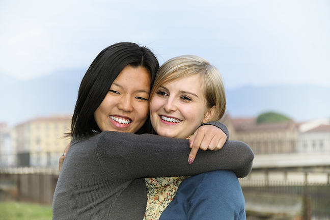 Asian and white women smiling and hugging