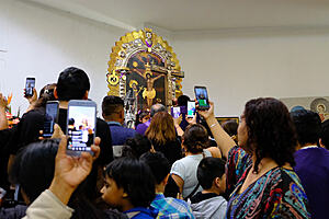 Interior of a church with a painting of the Christ, surrounded by people aiming their smartphones at the image. These are Peruvian migrants honoring in Chile the Lord of Miracles, the most revered Peruvian religious icon.