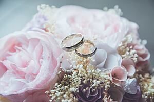 Two gold wedding rings sat on top of a bouquet of pink flowers