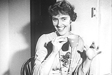 Joyce Grenfell smiling, holding a cup