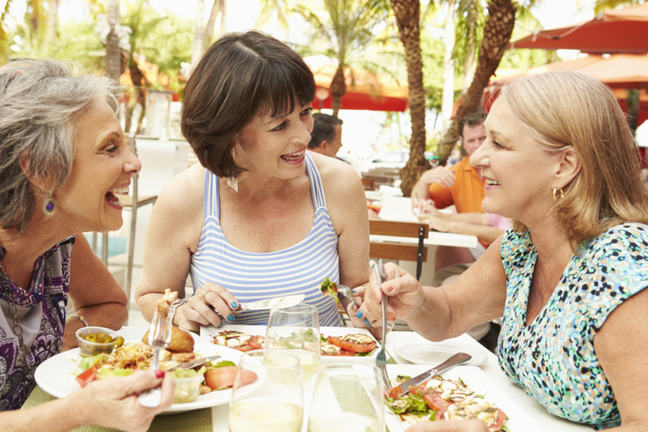 Three women sitting at a table outdoors eating food and talking.