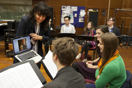 Photograph of choir members looking at an image on a computer screen