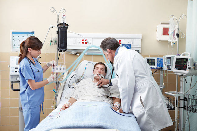 Unconscious patient in a hospital bed attended by health practitioners