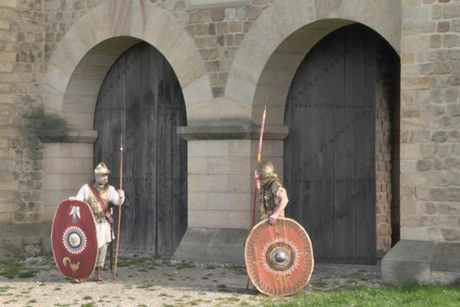 Photo of the reconstructed gate at Arbeia Roman Fort, South Shields with 2 students in costume as guards.