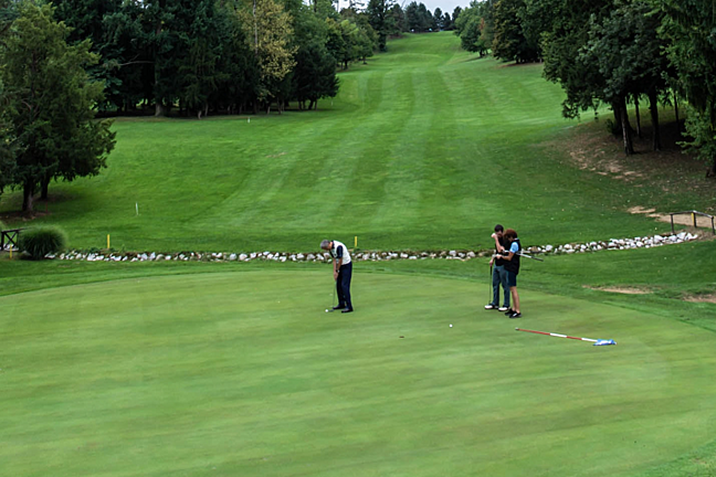 Two people watching a golf putt