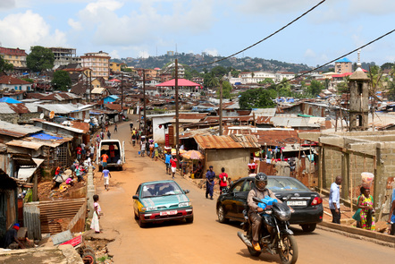 A busy street scene, with cars and a motorbike, in a Freetown settlement