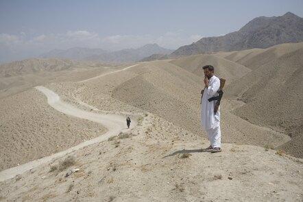 Afghan policemen look at the road leading to Spir Kundey.