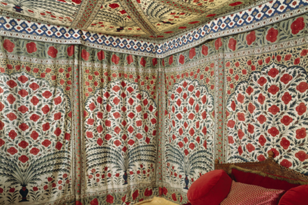 Cotton chintz with a white background, patterned with symmetrical flower arrangements, predominantly in reds and greens.