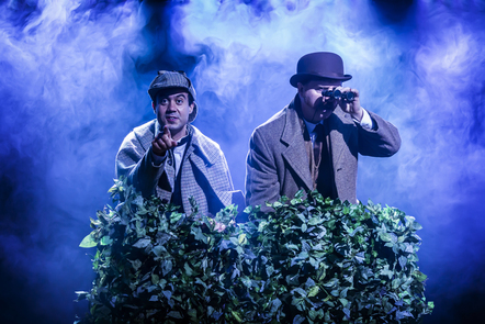 Two cast members on stage crouched behind a bush, one pointing out to the audience and one looking through a pair of binoculars