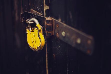 Yellow padlock on dark metal door
