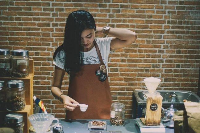 Young woman working at the counter in a coffee shop