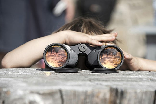 A child with binoculars that are reflecting the  Ceahlau Massif Durau - Romania