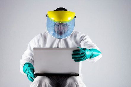 Man in a hazmat suit using a laptop