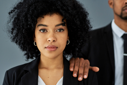 Woman staring into the camera with a mans hand placed on her shoulder