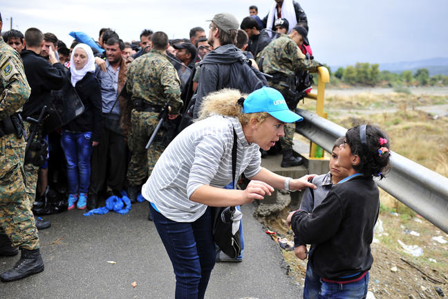 A woman with blonde hair and a blue UNICEF cap, white shirt and blue jeans is leaning down and talking to a young boy and girl. Behind them are women in head scarves and men, with soldiers in uniform and guns standing in front of them.