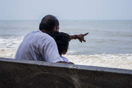 Grandfather sitting with grandson pointing at sea