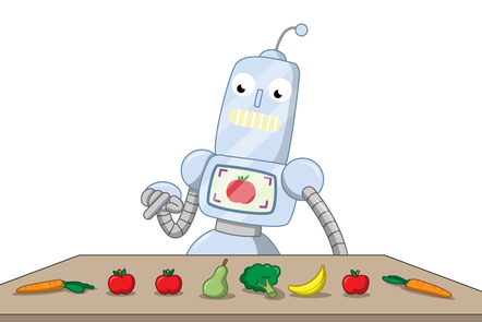 A robot has a set of fruit and veg on a table in front of it. It is pointing at one of the apples, which matches an apple displayed on a screen on the robot's chest.