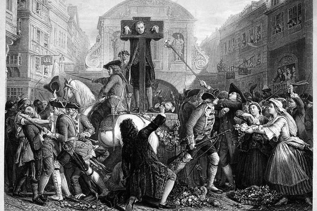 Daniel Defoe being held in a pillory while soldiers have to restrain crowds from throwing flowers at him