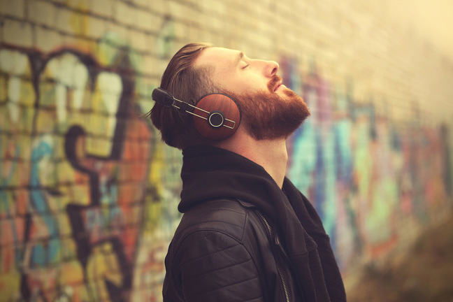 Young man listening to music through headphones outdoors against a background of colourful graffiti
