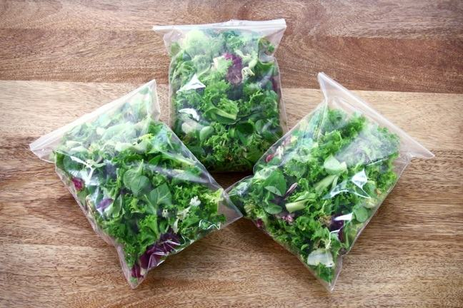 3 bags of salad on a wooden table